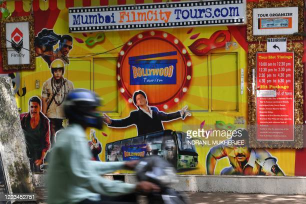 A motorist rides past the closed ticket counter of the Filmcity tour office adorned with images of Bollywood actors in Mumbai on June 29 2020...