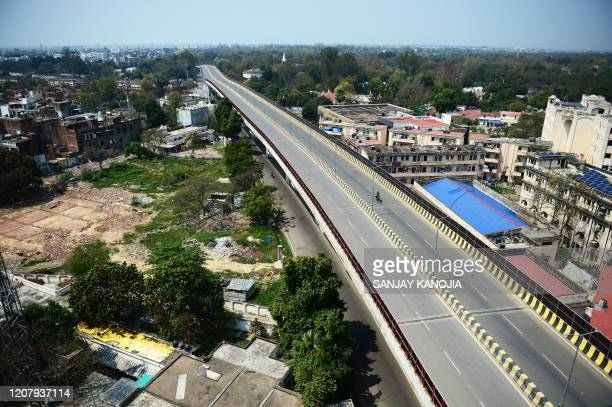 A motorist rides through a deserted flyover near Allahabad High court during a oneday Janata curfew imposed as a preventive measure against the...