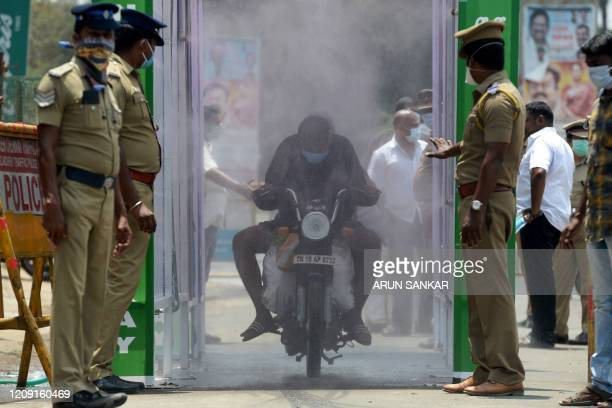 TOPSHOT A motorist rides through a disinfection tunnel during a governmentimposed nationwide lockdown as a preventive measure against the COVID19...