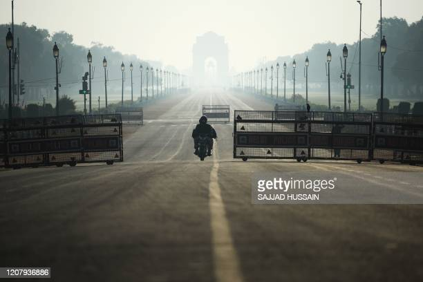 A motorist rides through deserted Rajpath road during a oneday Janata curfew imposed as a preventive measure against the COVID19 coronavirus in New...