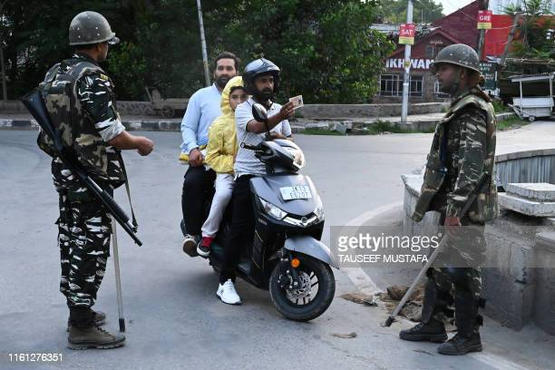 TOPSHOT A motorist shows his identity card to a security personnel after being stopped for questioning at a roadblock during a lockdown in Srinagar...