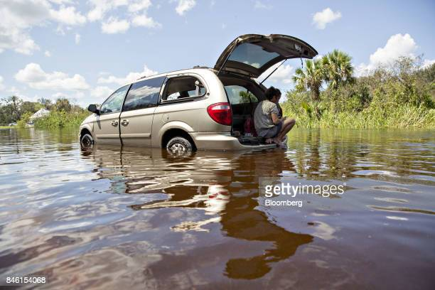 A motorist sits in the back of her minivan after failing to make it through a flooded road in Buckingham Florida US on Tuesday Sept 12 2017 Seven...