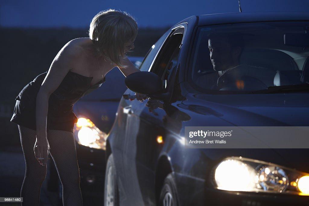 motorist talking to prostitute in street at night : Foto de stock