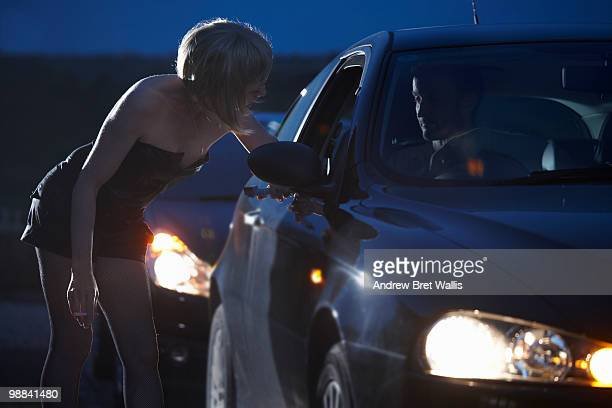 motorist talking to prostitute in street at night - hoeren stockfoto's en -beelden