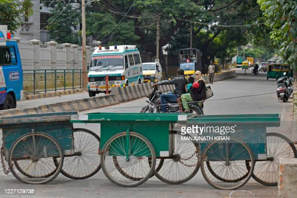 A motorist turns back next to a barricade of handcarts built across a road to restrict public movement during a weeklong lockdown to contain the...