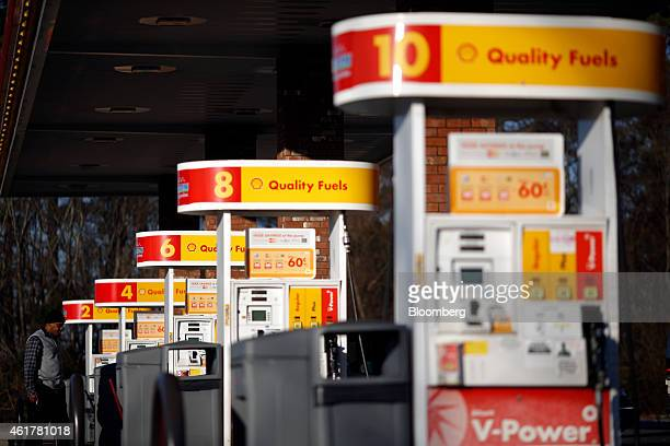 A motorist waits for his car to fill up with gasoline at a Royal Dutch Shell Plc gas station in Portland Tennessee US on Friday Jan 16 2015 Trips to...