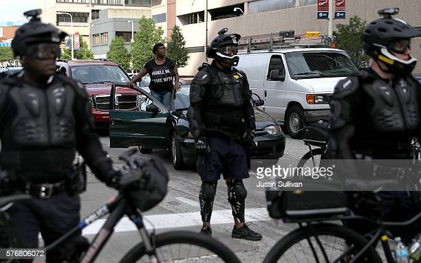 A motorist watches protesters from her car as Cleveland police officers block an intersection during a demonstration near the site of the Republican...