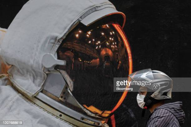 A motorist wearing a protective mask and helmet sits in front of a mural depicting an astronaut near Hollywood Road in Hong Kong China on Monday...
