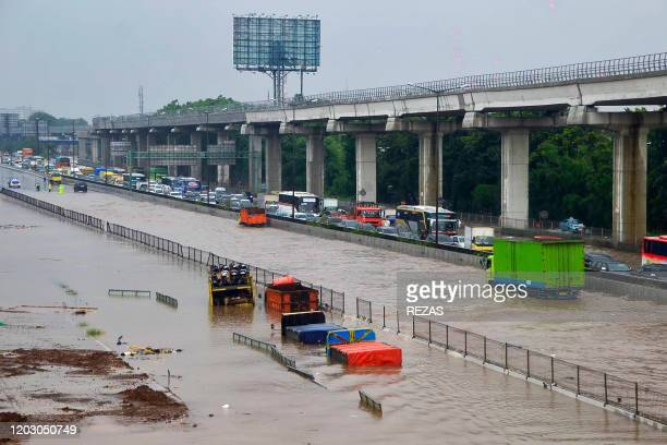 Motorists are seen trapped on a flooded toll road after heavy rain in Bekasi West Java on February 25 2020 Dozens of Jakarta neighbourhoods were...