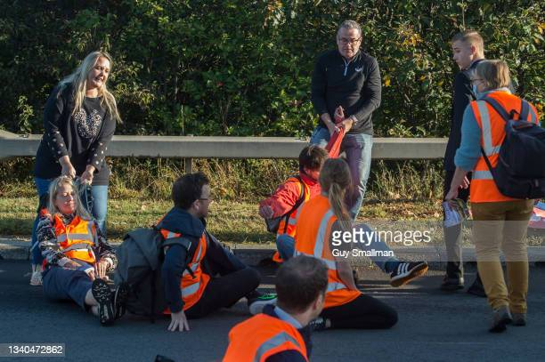 Motorists attempt to move activists as protesters from the Insulate Britain protest group block a major roundabout near the Dartford crossing and M25...