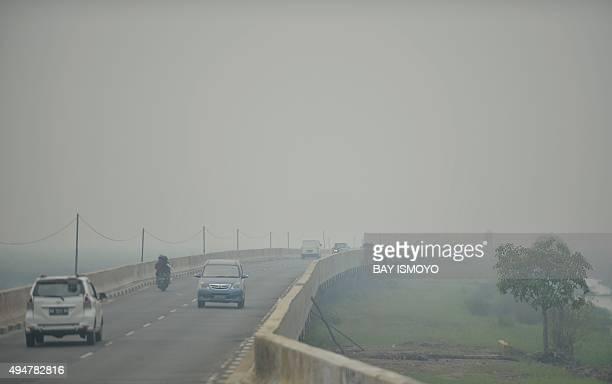 Motorists drive across the Tumbang Nusa bridge shrouded in haze some 20 kms on the outskirts of Palangkaraya in Central Kalimantan on October 29 2015...