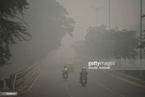 Motorists drive along a road under heavy smog conditions, in New Delhi on November 3, 2019. - India's capital New Delhi was enveloped in heavy, toxic...