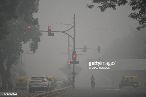 Motorists drive along a road under heavy smog conditions, in New Delhi on November 3, 2019. - India's capital New Delhi was enveloped in heavy, toxic...