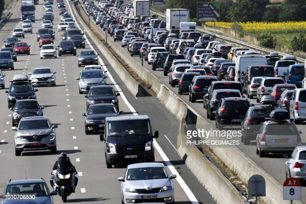 Motorists drive and queue in their vehicles on the A7 motorway near Vienne southeastern France on August 4 during a heavy traffic jam on the first...