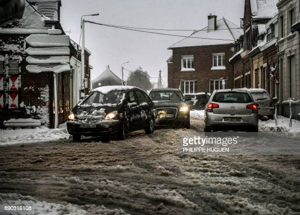 Motorists drive cars on a now covered road on December 11 in Godewaersvelde northern France / AFP PHOTO / PHILIPPE HUGUEN