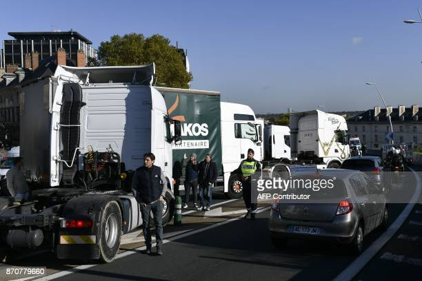 Motorists drive on one lane of the A13 highway as stallholders block the other side with their trucks during a goslow operation after being stopped...