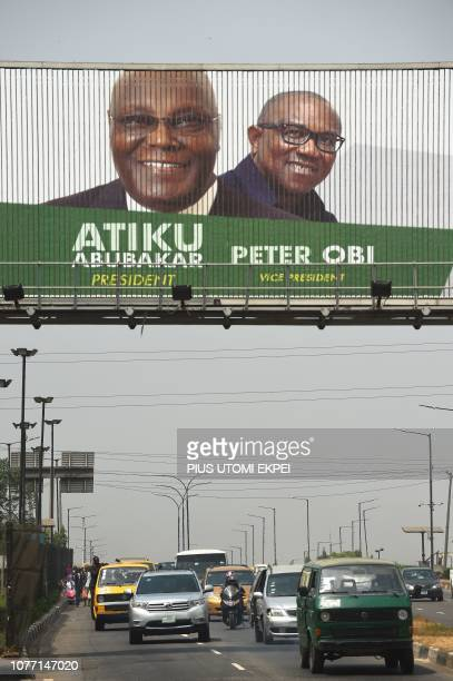 Motorists drive past a campaign billboard for Nigeria's presidential candidate of the opposition People's Democratic Party Atiku Abubakar and his...