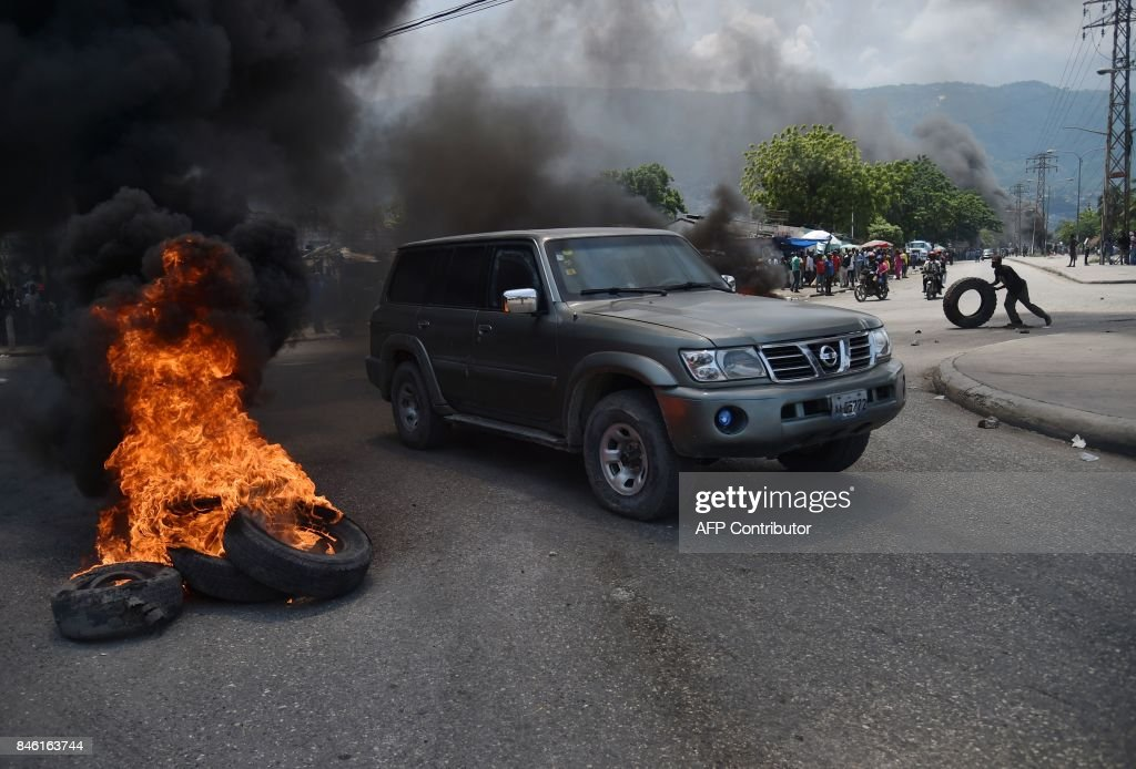 Motorists drive past burning tires placed by demonstrators during an anti-government protest in the centre of the Haitian capital Port-au-Prince, on September 12, 2017. Demonstrators took to the streets to protest against the government and the new budget for 2017-2018, throwing stones at the police, setting tires on fire and blocking some streets. /