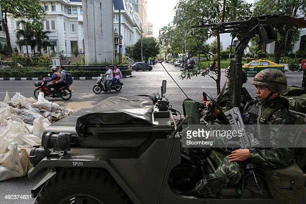 Motorists drive past Royal Thai Army soldiers stationed near luxury hotels on Ratchadamri Road in central Bangkok, Thailand, on Tuesday, May 20,...