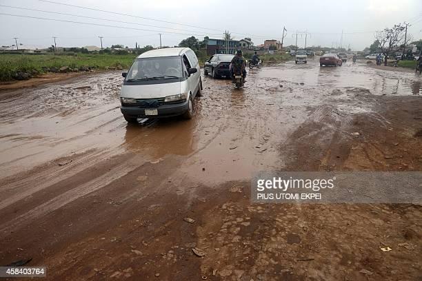 Motorists drive past waterlogged bumpy IkoroduShagamu road at Ogijo Ogun State on October 23 2014 Many roads lack proper drainage turning them into...