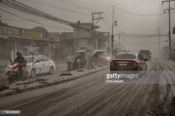 Motorists drive through a road covered in volcanic ash from Taal Volcano's eruption on January 13 2020 in Lemery Batangas province Philippines The...