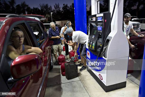 Motorists fill gas cans moments before the station was shut down by police due to a county wide curfew at a Marathon station in Estero Florida US on...