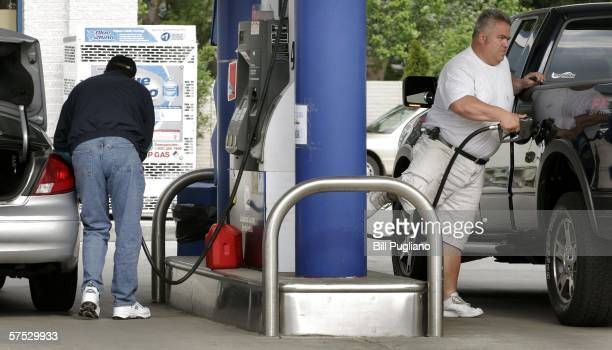 Motorists fill up their gas tanks after waiting for several hours in a three-mile long line to purchase gas at a fifty-cent discount a gallon at a...