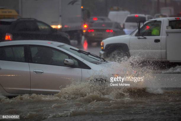 Motorists ford a flooded street as a powerful storm moves across Southern California on February 17 2017 in Sun Valley California After years of...