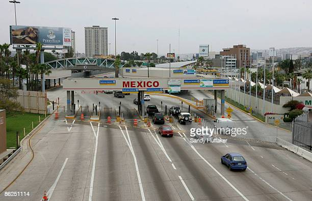 Motorists head into Mexico at the border on April 27 2009 in San Ysidro California US Health officials advises Americans to avoid all nonessential...