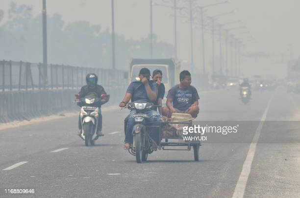 TOPSHOT Motorists make their way along a street in Kampar Riau on September 17 2019 which is covered in thick haze Indonesia is battling forest fires...