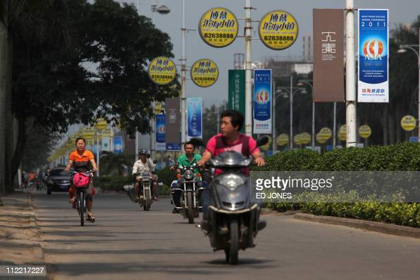 Motorists make their way down a road past banners advertising the Boao Forum for Asia, taking place nearby, in the southen Chinese city of Qionghai...