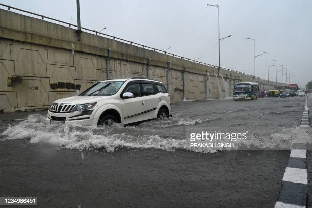 Motorists make their way on a waterlogged road during heavy rains in New Delhi on September 1, 2021.