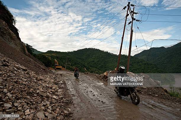 Motorists make their way through a damaged portion of the SiliguriGangtok National Highway on September 19 after a 69magnitude earthquake hit the...