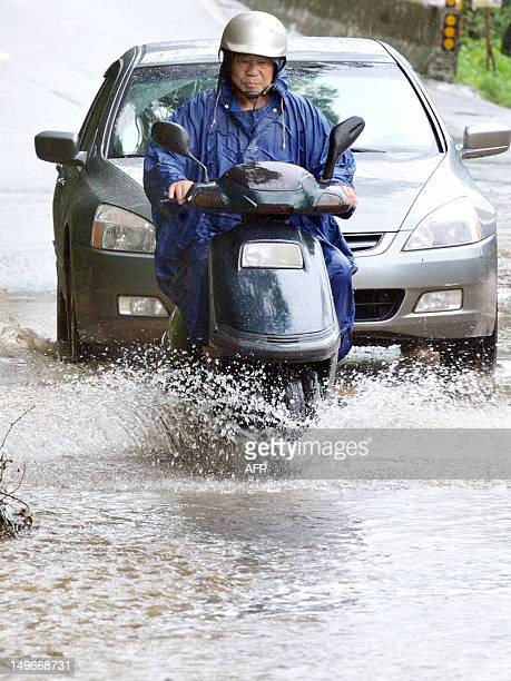 Motorists maneuover through floodwaters on a road in New Taipei City on August 2 2012 Typhoon Saola pounded Taiwan with fierce winds and torrential...