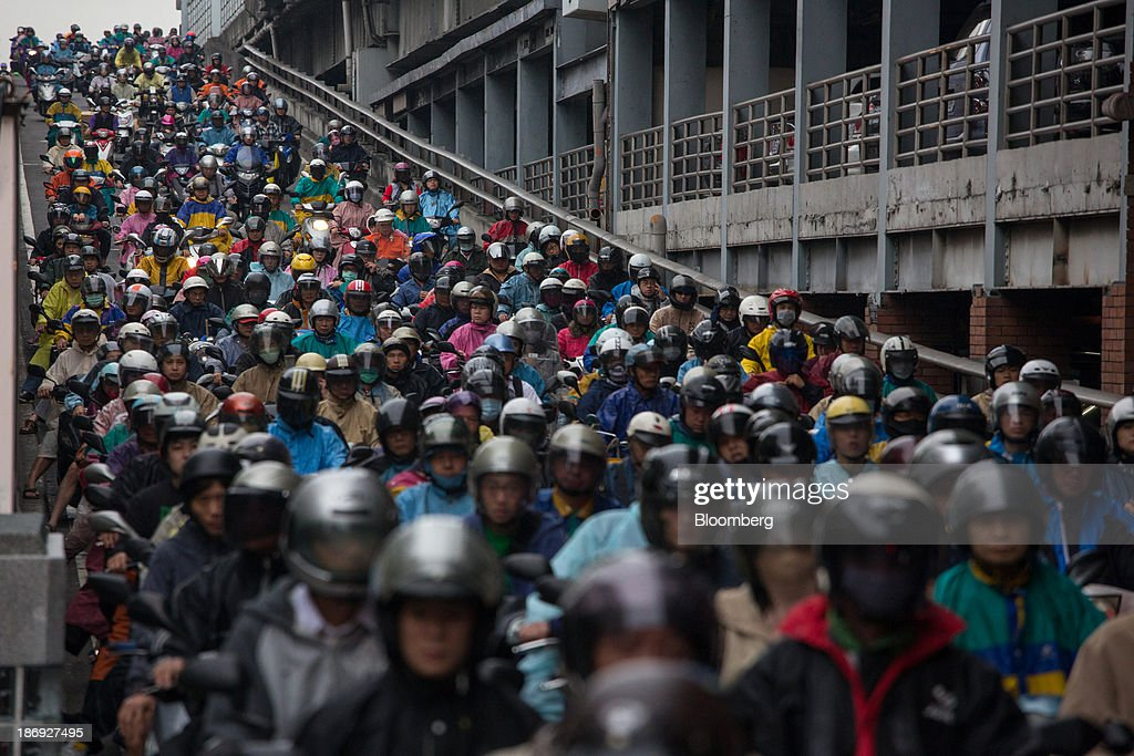 Motorists on motorcycles sit in traffic on a bridge in Taipei, Taiwan, on Monday, Nov. 4, 2013. Taiwans five-year bonds gained for the first time in four days, lowering the yield from a three-week high, after a report showed inflation cooled. The local dollar strengthened. Photographer: Lam Yik Fei/Bloomberg via Getty Images