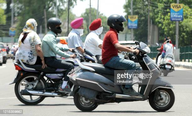 Motorists out with their faces covered on a hot summer day on May 26, 2020 in Patiala, India.