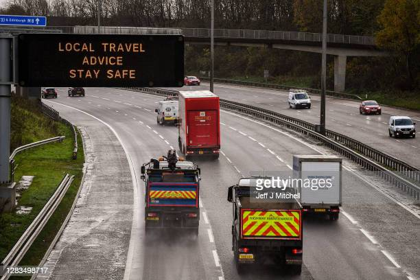 Motorists pass a motorway gantry sign on the M8 on November 02, 2020 in Glasgow, Scotland. Scotland is proceeding with a regional, five-tier approach...