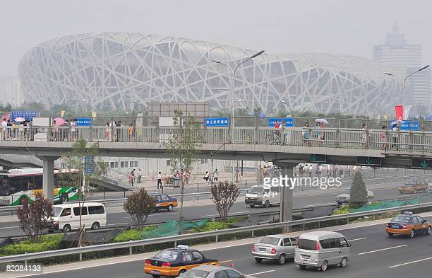 """Motorists pass in front of the National Stadium also known as """"Bird's Nest"""" engulfed by thick smog in Beijing on July 28, 2008. Beijing is..."""
