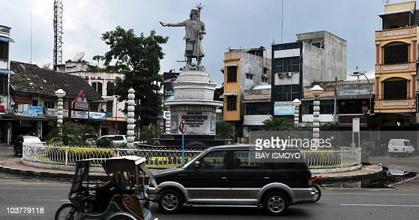 Motorists pass the Guru Patimpus statue in downtown Medan the capital city of North Sumatra on September 2 2010 Guru Patimpus was the founder of...