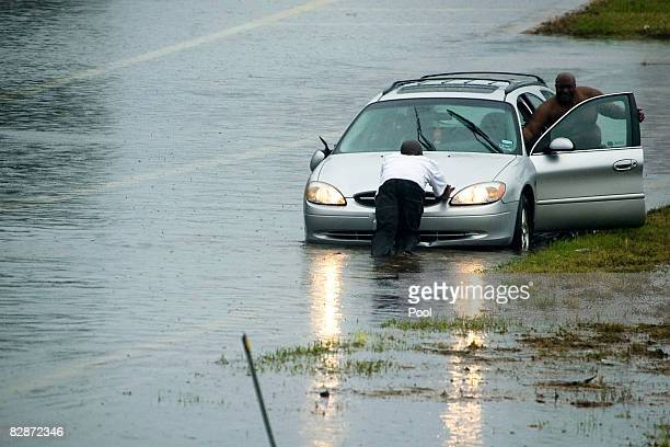 Motorists push a vehicle from high water during early morning rains in the wake of Hurricane Ike September 14 2008 in Houston Texas Floodwaters from...