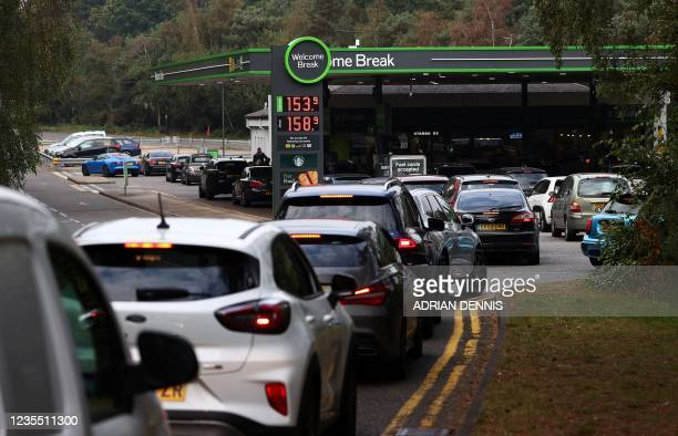Motorists queue for petrol and diesel fuel at a petrol station off of the M3 motorway near Fleet, west of London on September 26, 2021. - Britain's...