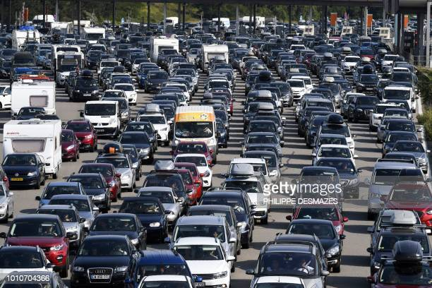 TOPSHOT Motorists queue in their vehicles at a toll station on the A7 motorway near Vienne southeastern France on August 4 during a heavy traffic jam...