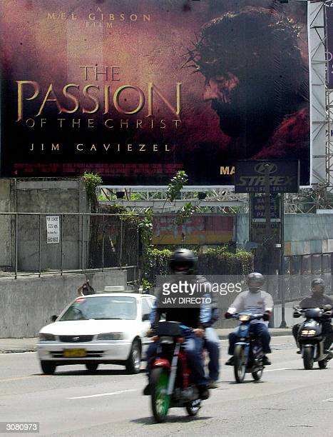 Motorists ride past a billboard advertising the controversial movie directed by Mel Gibson the Passion of the Christ displayed along a street in...