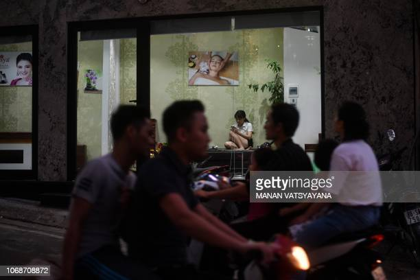 TOPSHOT Motorists ride past as a Vietnamese beautyparlour attendant checks her mobile phone while waiting for customers in Hanoi on December 5 2018