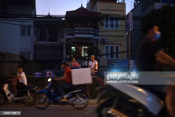 Motorists ride past as a Vietnamese man sits at a roadside foodstall in Hanoi on December 5 2018