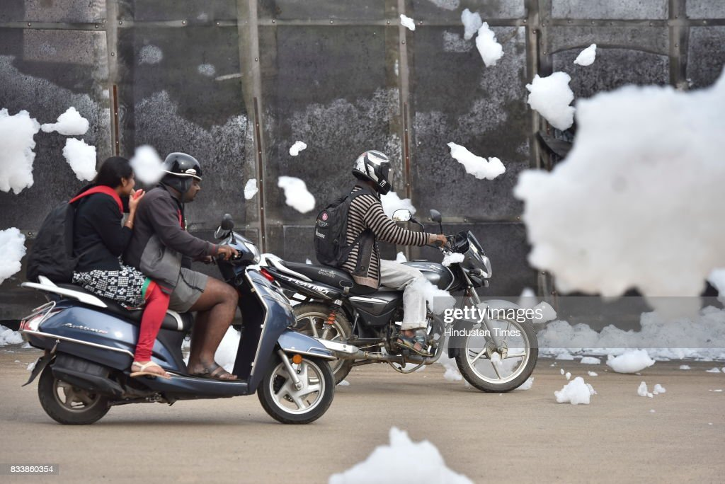 Motorists ride through the flying froth from the polluted Bellandur Lake on August 17, 2017 in Bengaluru, India. Rapid urbanisation is taking its toll, between 2001 and 2011, the city's population increased from 6.5 million to 9.6 million, the highest rate of growth of any city in India. The indiscriminate discharge of household waste and industrial effluents into lakes is what causes the toxicity, leading to the water body foaming. According to a report by the Karnataka State Pollution Control Board, of the 67 lakes surveyed in Bengaluru, none had water that was fit for drinking.