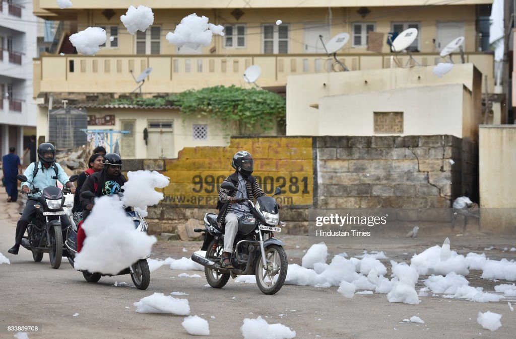 Motorists ride through the flying froths from the polluted Bellandur Lake on August 17, 2017 in Bengaluru, India. Rapid urbanisation is taking its toll, between 2001 and 2011, the city's population increased from 6.5 million to 9.6 million, the highest rate of growth of any city in India. The indiscriminate discharge of household waste and industrial effluents into lakes is what causes the toxicity, leading to the water body foaming. According to a report by the Karnataka State Pollution Control Board, of the 67 lakes surveyed in Bengaluru, none had water that was fit for drinking.