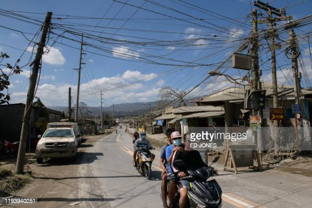 Motorists ride towards a roadblock as they leave a restricted area due to the eruption of the nearby Taal volcano in Talisay on January 16 2020 The...