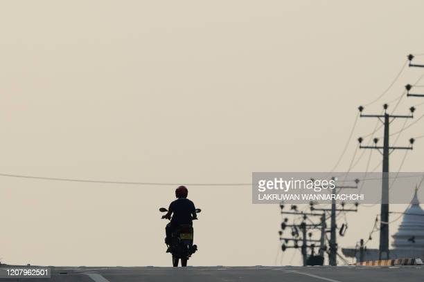 A motorists rides along a deserted street during a nationwide weekend curfew imposed as a preventive measure against the spread of the COVID19...