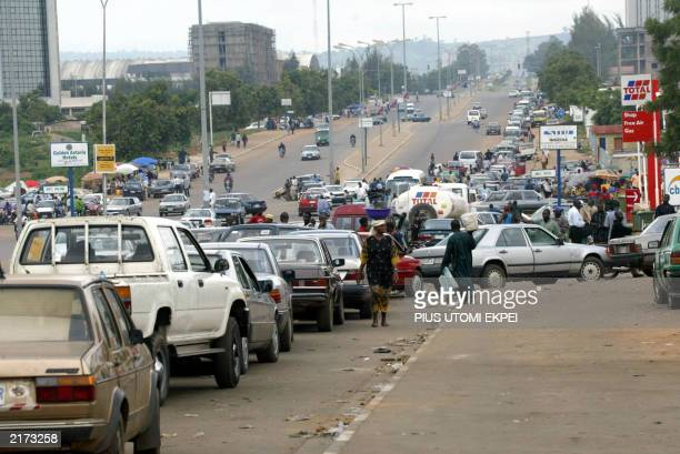 Motorists rush to buy petrol at a station following a weeklong strike over fuel prices 10 July 2003 in Abuja US President George W Bush will arrive...